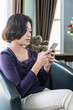 Young asian woman short hair use mobile phone in living room