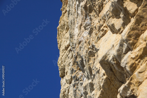 Tuinposter Beige great rock wall, cliff against the blue sky