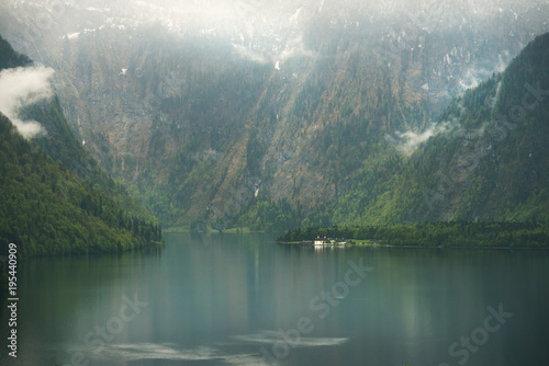 View over misty Lake Konigssee with tiny St Bartholomae church in Berchtesgaden National Park, Bavaria, Germany