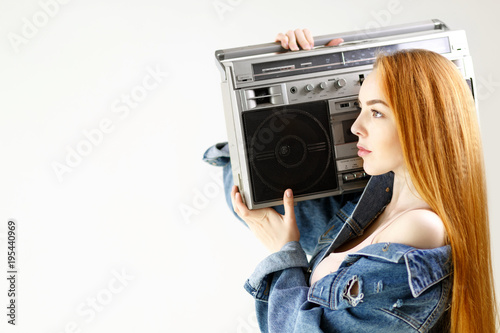 beautiful red-haired woman in a denim jacket holding retro tape recorder on a white background