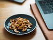 Some cashew nuts on small snack dish on work desk.