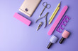 Set of cosmetic tools for manicure and pedicure on a purple background. Gel polishes, nail files and clippers, top view