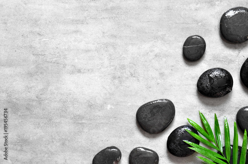 Grey spa background, palm leaves and black wet stones, top view