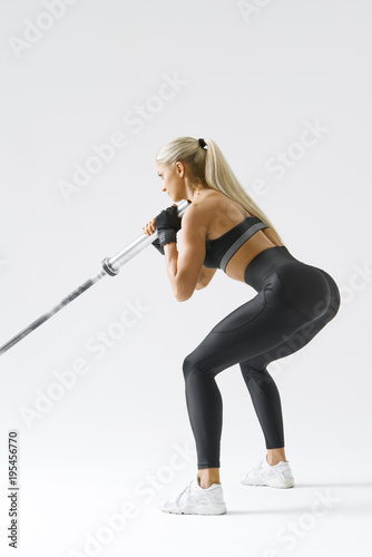 Rear view of female athlete lifting heavy weights Image of attractive woman with barbell Bodybuilder female model performing barbell squat Confident young woman exercising with barbell.