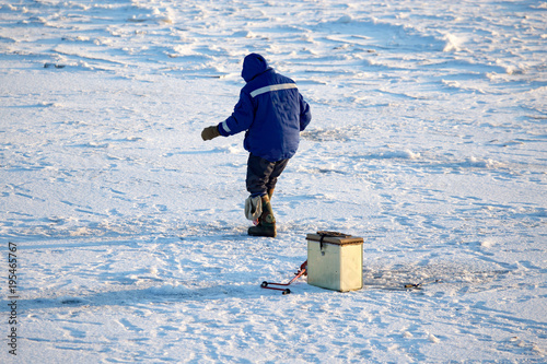 Foto op Canvas Natuur A man on ice is fishing in the evening