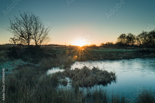 Foto op Canvas Natuur A starburst of dawn light breaking on a frozen pond on Wetley Moor Staffordshire.