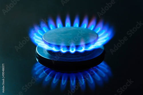 The gas is burning, the gas-stove burner, the hob in the kitchen, close-up. The concept of problems with natural gas, rising gas prices.