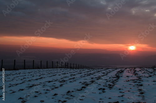 Tuinposter Zee zonsondergang winter beauty sunset over hills