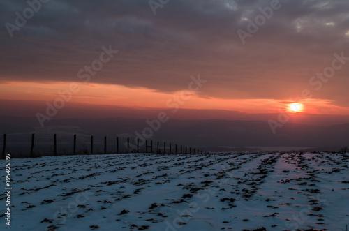 Staande foto Zee zonsondergang winter beauty sunset over hills