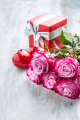Roses. Pink roses with two hearts and red gift.