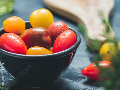 Aluminium Kersen Colorful cherry tomatoes in a black bowl in a kitchen.
