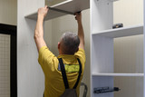 the master installs a wardrobe in apartment - 195504320