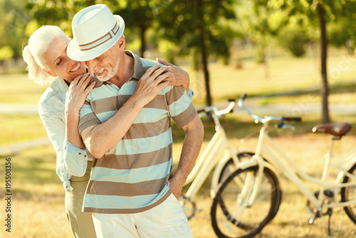Retired couple. Joyful positive aged man looking at his wife and smiling while enjoying his time together with her