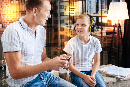 Aluminium Muziek Favorite song. Positive friendly young man sitting on the table with a modern smartphone in his hands while his kind smiling son sitting by his side with big headphones on his head and looking at him