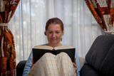 Mujer sentada en su sofá y tapada con una manta lee un libro - 195516915