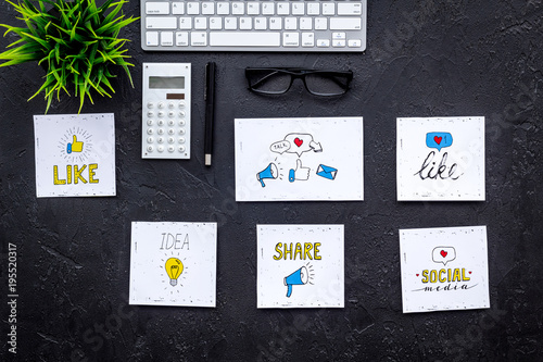 Social media promotion. Work desk with socail media icons. Black background top view