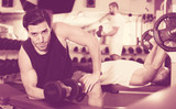 Guy during workout in gym with dumbbells - 195529375