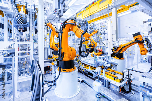 Leinwanddruck Bild robotic arms in a car plant