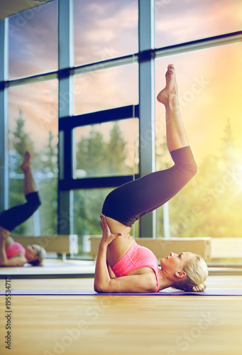 woman doing shoulderstand on mat in gym