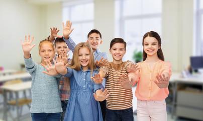 happy students waving hands at school