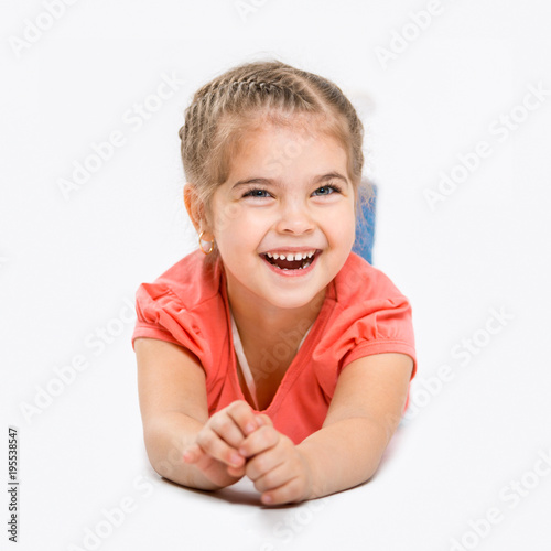 Portrait of a beautiful little cheerful girl. The child laughs