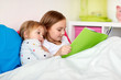 little girls or sisters reading book in bed - 195538729