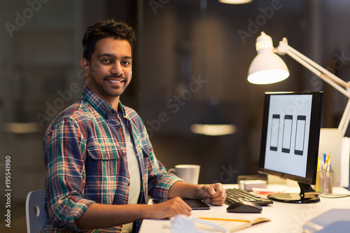 designer with computer working at night office
