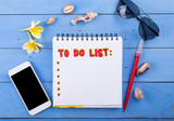 Beach accessories/utilities : black to do list notebook, phone, eyeglasses, sea shell and plumeria flowers on blue wooden background - 195577593