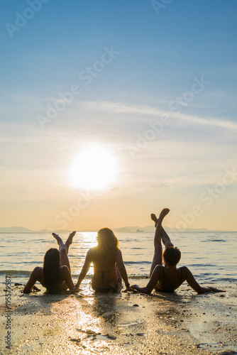 Silhouette of three girls on the beach at sunset