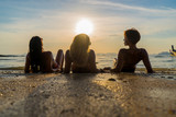 Silhouette of three girls on the beach at sunset - 195579765