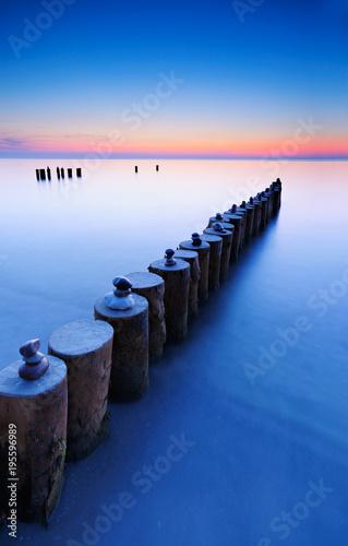 Foto op Aluminium Stenen in het Zand Buhnen mit Steinpyramiden am Strand der Ostsee bei Sonnenuntergang, Darß, Deutschland