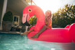 Girl on a pink flamingo in the pool