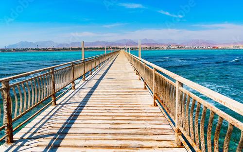 Opuszczone molo morskie, prowadzące na odległość. Zardzewiały balustrada. Stare drewniane deski. Widok na górski brzeg. Coudy błękitne niebo. Słoneczny dzień.