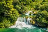Piękny wodospad wśród zielonych drzew. Krajobraz w paku Krka w Chorwacji.
