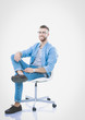 Young man sitting on the chair isolated over white background. Startupper. Young entrepreneur.