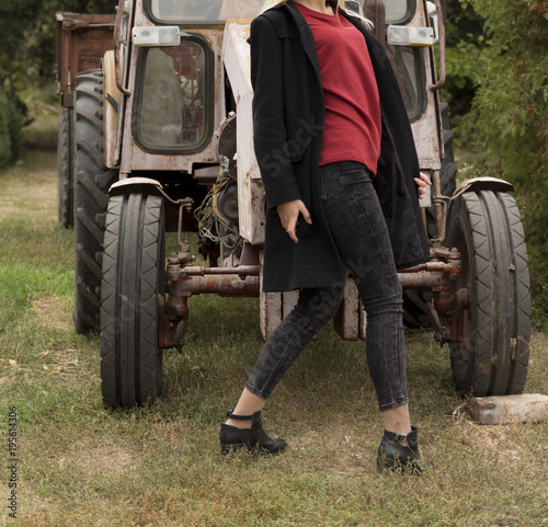 Aluminium Trekker a girl in a black coat and a red jacket is standing near a tractor on a green grass
