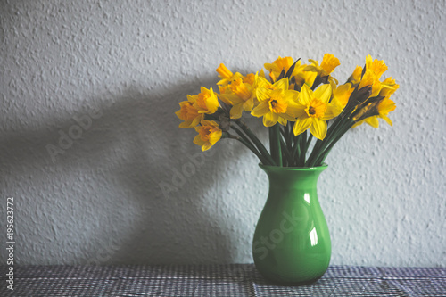 A bunch of yellow daffodils in a green vase