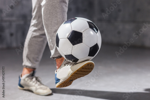 Fotobehang Voetbal Man holds a soccer ball on his leg. Close-up