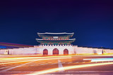 Famous Gwanghwamun gate of Gyeongbokgung Palace in Seoul, South Korea with taillights and headlights of cars in front of it - 195632725