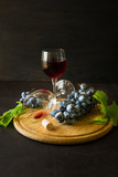 Two wineglasses with red wine and grapes decorated vine leaves on dark wooden desk - 195640985