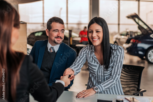 Wall mural Smiling woman buying car at showroom. Car saleswoman and customer handshake.