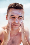 Young man putting tanning cream on his face, sunbathing on the beach. Healthcare. - 195647538