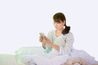 Asian women playing mobile phones On Her White Bed While Waking Up.Isoleted Dicut Clipping Path Image.