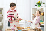 Mother and daughter cooking at home, making the dough for buns - 195658377