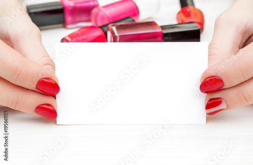 Foto op Canvas Manicure Female's hands with red manicure holding business card and bottles with nail polish on white wooden table.