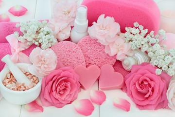 Beauty treatment cleansing and ex foliation products with pink rose and carnation flowers, ex foliating salt, heart shaped soaps, body lotion, seashell soaps, sponges, wash cloths and seashells.