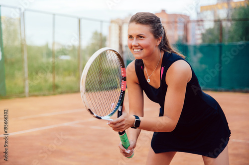Aluminium Tennis Tennis player. Attractive young woman standing with racket in ready stance to receive ball, while playing tennis. Dressed in black sportswear.