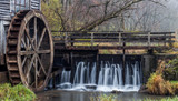 Flowing water over a damn with water wheel