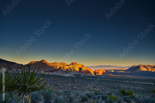Poster Las Vegas sun setting over redrock canyon rocks with las vegas in background