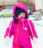 Toddler baby girl in a magenta snow suit playing on the snow. - 195683940